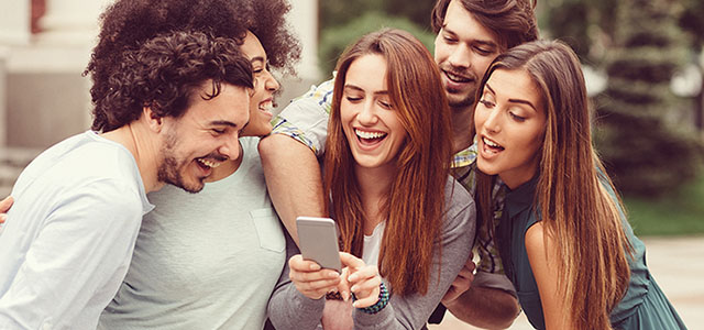Group of people around a mobile phone