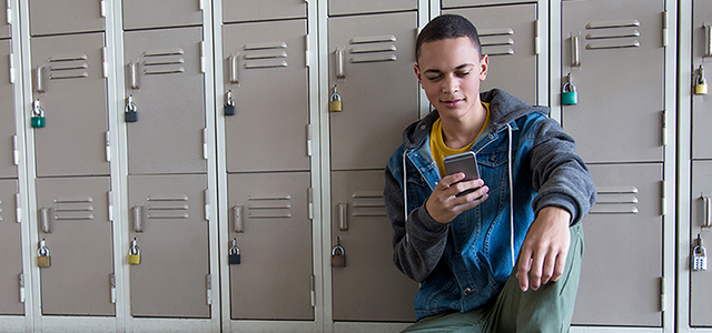 Boy on his mobile phone near lockers