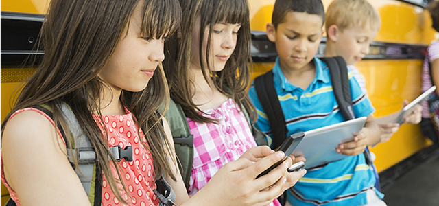 Kids on mobile devices near a school bus